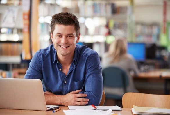 A VU Online Master of Financial Planning student sits smiling at a table with a laptop and documents.