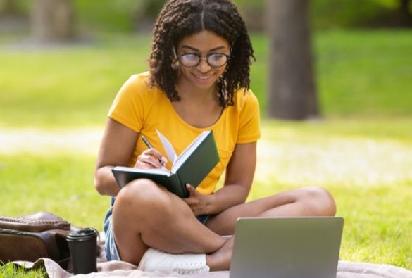 A VU Online student studies outside.