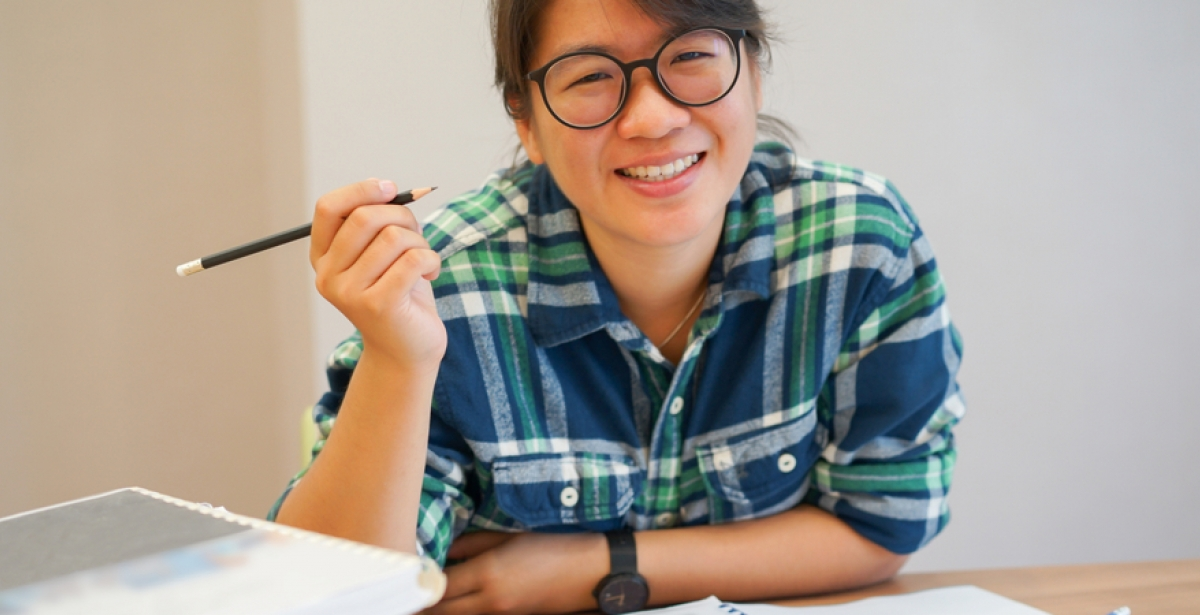 A VU Online MBA student surrounded by study materials holds up a pencil and smiles.