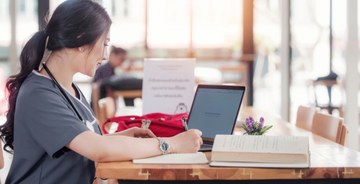 A VU Online Master of Nursing student sits at a desk with her laptop.