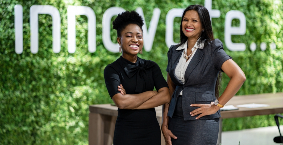 Two business leaders stand in front of a sign that says 'innovation.'